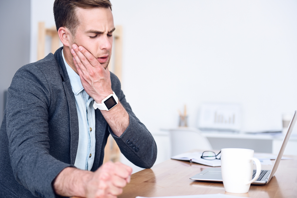 younger man suffering from TMJ at work